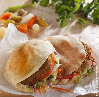 Falafel, or ta'ameya (طعمية) sandwich, crunchy ta'ameya with green salad , dressed with tahini , served with pickles. Egyptian Fast Food ! yum!