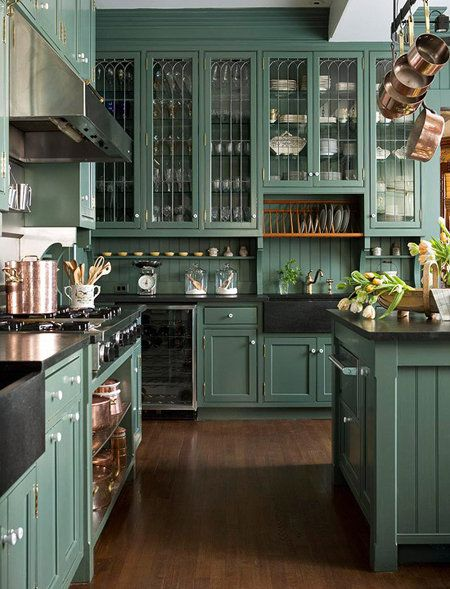 Smoky green cabinetry with pretty white porcelain hardware creates a cozy feel in this kitchen. The hanging copper pots really shine against the cabinetry color.  Source