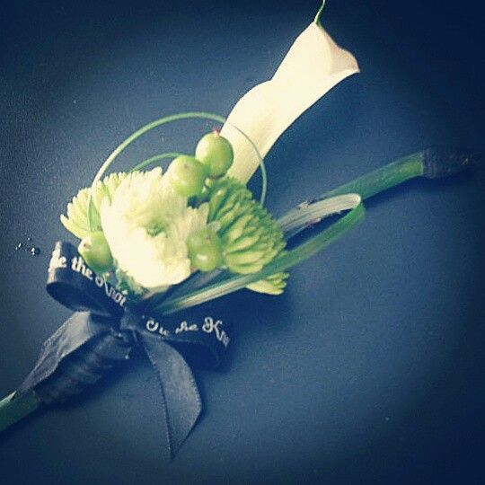 Tie the knot Groom boutonniere of a white calla and green mums and hypericum. A stem of horsetail and a loop or two of bear grass completes the knot