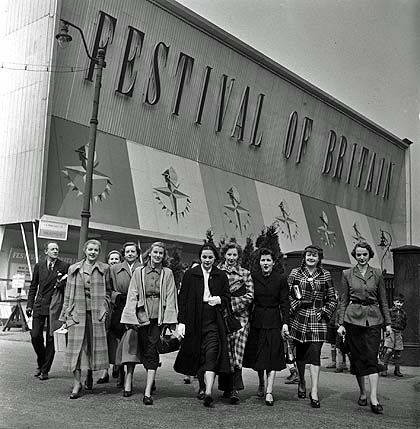 a photo of a group of women dressed in 1950s clothes outside a building  with a