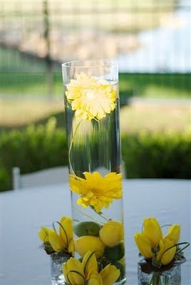 Lemons and limes with gerbera daisies submerged in a taller vase.