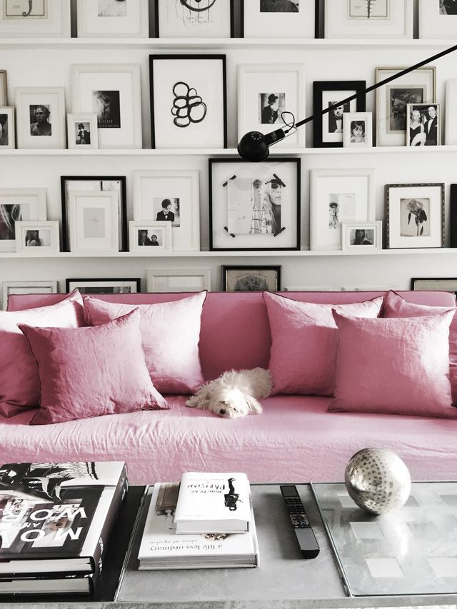Pink sofa with shelves filled with black and white framed art. Brilliant alternative to a gallery wall!