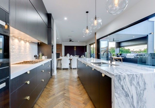 Modern Custom Built Kitchen with a stone bench top with waterfall end. Kitchen renovations Gold Coast.