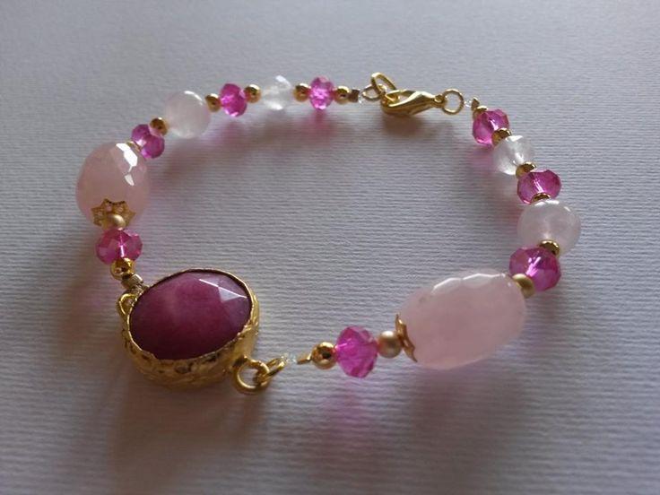 Bracciale con quarzo rosa, cristalli e centrale di agata fucsia, montato con componenti in metallo coloro oro. Realizzazione artigianale.