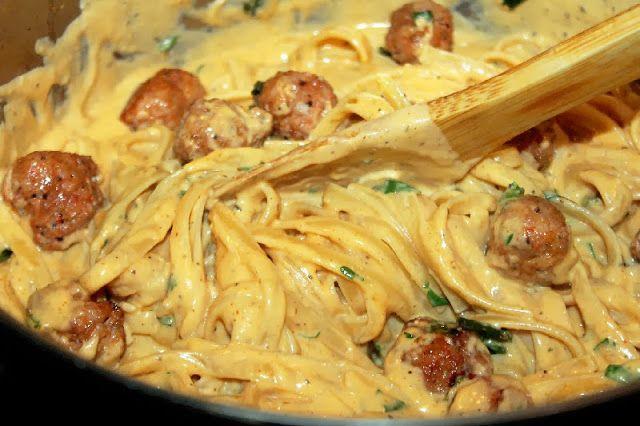 Запеченный Фетучини Альфредо 1 кг феттучини макаронные 1 фунт итальянс колбаса,  2 чашки жирных сливок. 1/2 стакана молока. тертый 1 стакан сыр моцарелла, тертый 1 стакан Пармиджано Реджано сыр,  2 ч. ложки черного перца, 2 ч ложки креольской приправы 2 чайные ложки чесночного порошка 2 ч.л. луковый порошок 2 чайной ложки паприки 4 стебля зеленого лука, нарезанные 3 столовые ложки  петрушки, фарш 3 зубчика чеснока, измельчить 2 ст/л оливкового масла 2 ст/л сливочного масла 4 ст/л муки