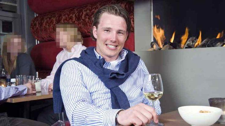Ein junger Mann sitzt lächelnd auf einem Stuhl und greift nach einem Glas Wein