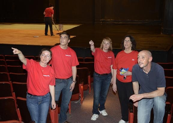 Key Bank employee volunteers, from left, Kathy LaCross, Jordan Flores, Mary Pellerin and Donna Cork ask Home Made Theater Technical Director Kevin Miller, right, questions about the Spa Little Theater as its stage gets a fresh coat of paint. Nationwide, more than 7,500 Key Bank employees participated in Neighbors Make a Difference Day. (ED BURKE)