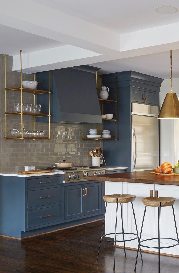beautiful kitchen with a glossy tile backsplash, dark blue cabinets, open shelving, modern lighting