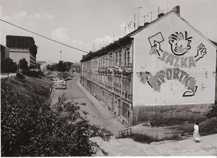 Sirková ulice na snímku z roku 1986. O rok později byly domy převážně z 19. a začátku 20. století zbořeny a na jejich místě vznikl podchod a silnice s tramvajovými kolejemi.
