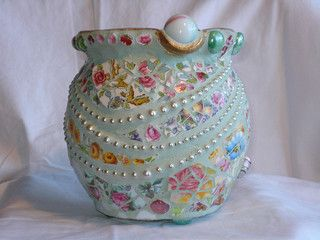 "Beautiful mosaic pot. From the website ""... soft colors are very old fashioned and romantic. Triple strand of pearls and red crystals add an elegant feminine touch. It was sold out of Pam Nelson's gallery in Takaka, New Zealand. China, glass beads, crystals, marbles, glass bobbles, pearls. Approx. 6 inched high."" Poppins Mosaics and Crafts"
