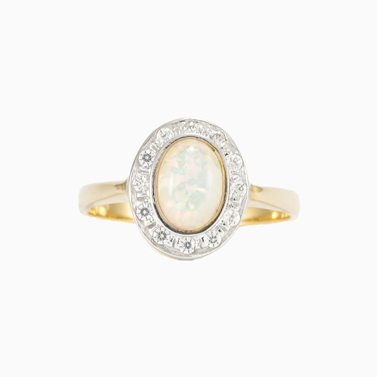 A beautiful vintage style ring in 14k gold with a halo of round crystals that accentuate the cabochon Opal.