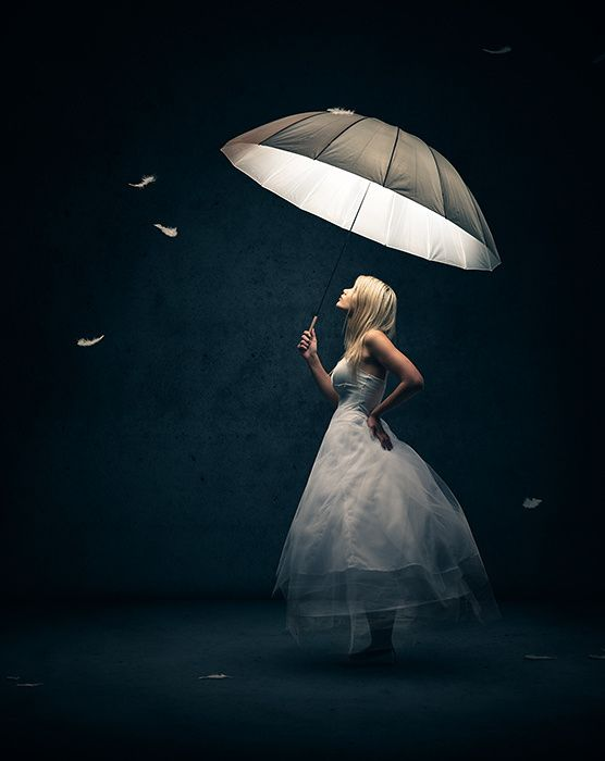 Girl dressed in white with light emitting umbrella looking up at falling feathers