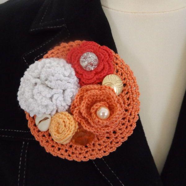 Romantikus hangulatú, vintage kitűző horgolt virágokkal, valamint gyöngyökkel és gombokkal csipke alapon.