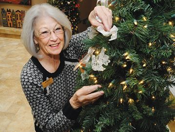 Celebrating lives lived in Barrie - Sharon Bowden, one of the volunteers at Hospice Simcoe, puts one of the angels on the tree.