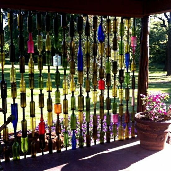 Upcycled Garden Style. . . Upcycled bottle wall. Drill a hole in the bottom of about a zillion bottles, thread rebar through them, then install.