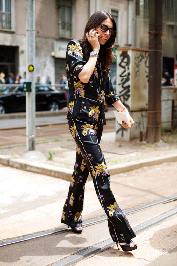 Viviana Volpicella atravessa a rua usando look todo de pijama de seda floral, salto alto preto e óculos escuros