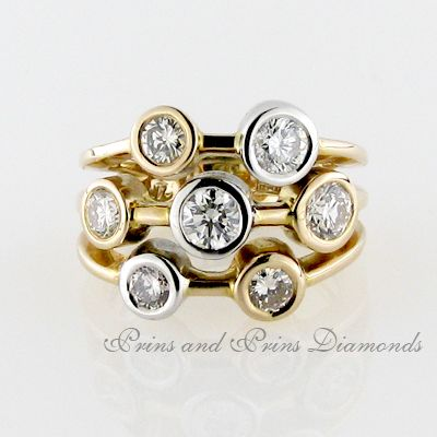 There are 7 = 1.87ct round brilliant cut diamonds of various clarities and colours tube set in 18k rose gold in a three row ring design