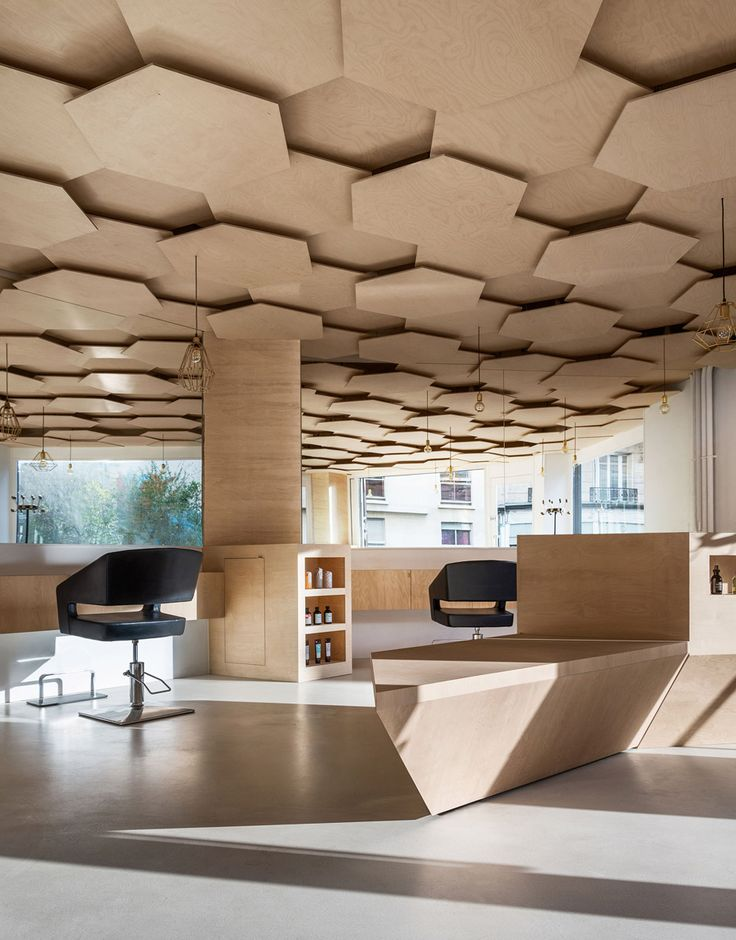 Sheets of plywood were layered to create the ceiling within this Parisian salon, which architect Joshua Florquin designed to represent natural environments.