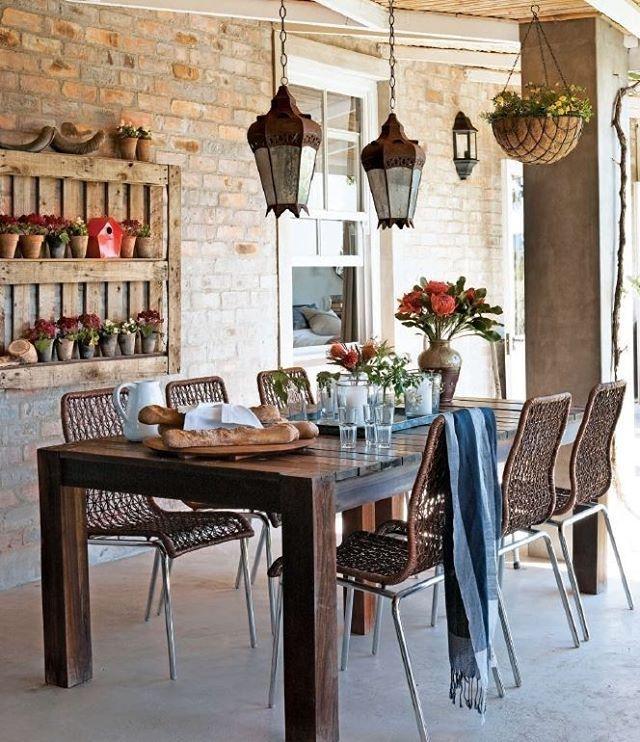 Na varanda desta casa, na África do Sul, uma composição com plantas suspensas e vasos pendurados na parede compõem o décor. A mesa de teca, as cadeiras de fibra e as lanternas de aço ajudam a compor a decoração rústica do espaço. Foto Micky Hoyle e Adam Letch/ surpressagency #decoraçãorústica #mesanavaranda #mesaoutdoor #outdoorarea #mesademadeira