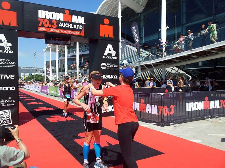 Chantal, 13, with ALL, gets to hand out the medals at the 2014 IRONMAN 70.3 Auckland finish line