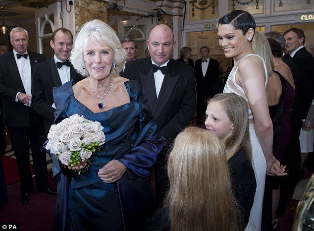 Flower girl: Camilla looked radiant as she carried a bouquet of flowers after meeting guests and performers