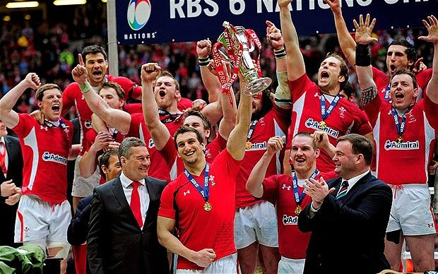 Wales captain Sam Warburton shrugs off an injured right shoulder to hoist the Six Nations trophy aloft after sealing the Grand Slam