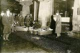 Picture shows police or fire officials placing Triangle Shirtwaist Company fire victims in coffins. (March 25, 1911)