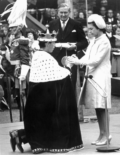 Queen Elizabeth II holds the hands of her 20-year-old son Prince Charles during his investiture as Prince of Wales, 11 July 1969, at Caernarfon castle (in Wales), as demanded by tradition.