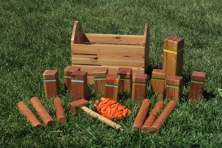 """Kubb (pronounced """"koob"""") is a lawn game where the object is to knock over wooden blocks, known as 'kubbs,' by throwing wooden batons at them. This DIY set includes """"regulation-sized"""" kubbs, batons, a king, stakes on a pre-measured line for marking the field, and a case with an integrated mallet."""