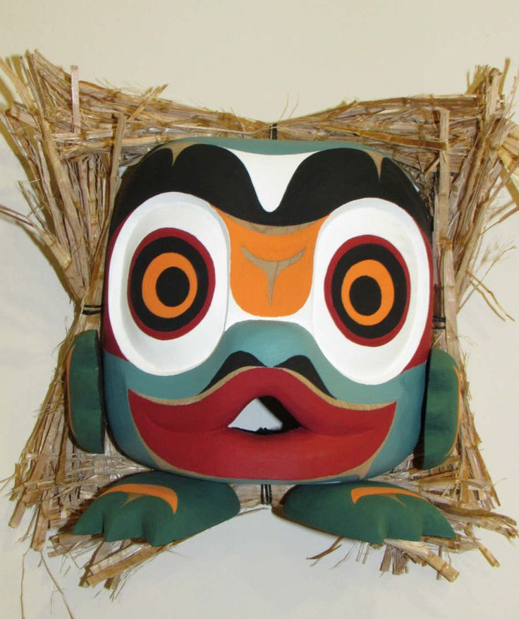 This mask was hand carved by #Northwest #Coast #FirstNations artist Rupert Scow. The frog brings great wealth and is known for its adaptability, knowledge and power as frog travels and lives in two worlds, water and land.  Carved out of red cedar, painted with acrylic paint, and cedar bark bunches around the edge. Can be stood on flat surface or hung on the wall. #AboriginalBC