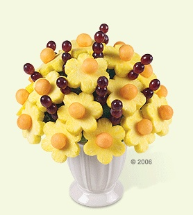 Pineapple & cantalope daisies with grapes on skewers.