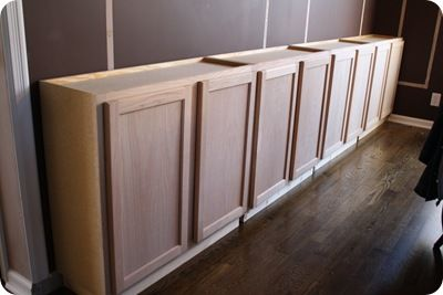 Using upper cabinets for the base of built-in bookcases.....or.....put a top on it for a buffet....with open shelving above....What a great idea!