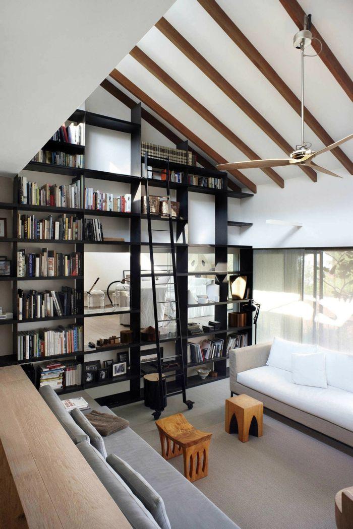 estanterias originales, salón moderno, techo con vigas, decoración en blanco y negro, estantería de suelo a techo como separador de ambientes, lámpara ventilador, sofá blanco y gris