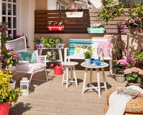 Terraza con alfombra de sisal, macetas, flores y cojines de colores y a rayas, mesas de centro y pared de lamas de madera horizontales