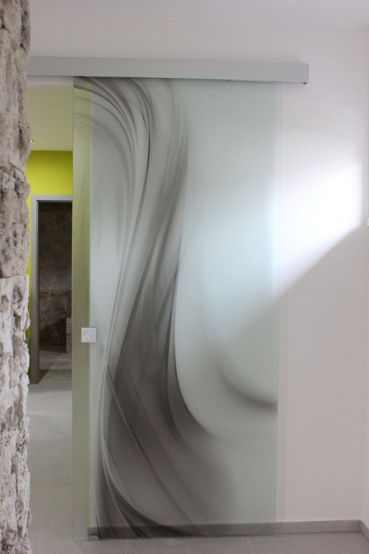 Realizácia sklenených posuvných dverí z kategórie MAT vytvorené digitálnou tlačou na matnom skle Satinato. Sklenené dvere sú z kaleného lešteného skla hrúbky 8 mm. Posuvné dvere sú osadené v posuvnom systéme Slido Classic, montáž L2 s obojstrannými tlmeniami, na uchopenie je osadená hliníková mušľa štvorcová. Abstraktný dizajn dverí tvorí moderný vzhľad bývania v novom rodinnom dome.
