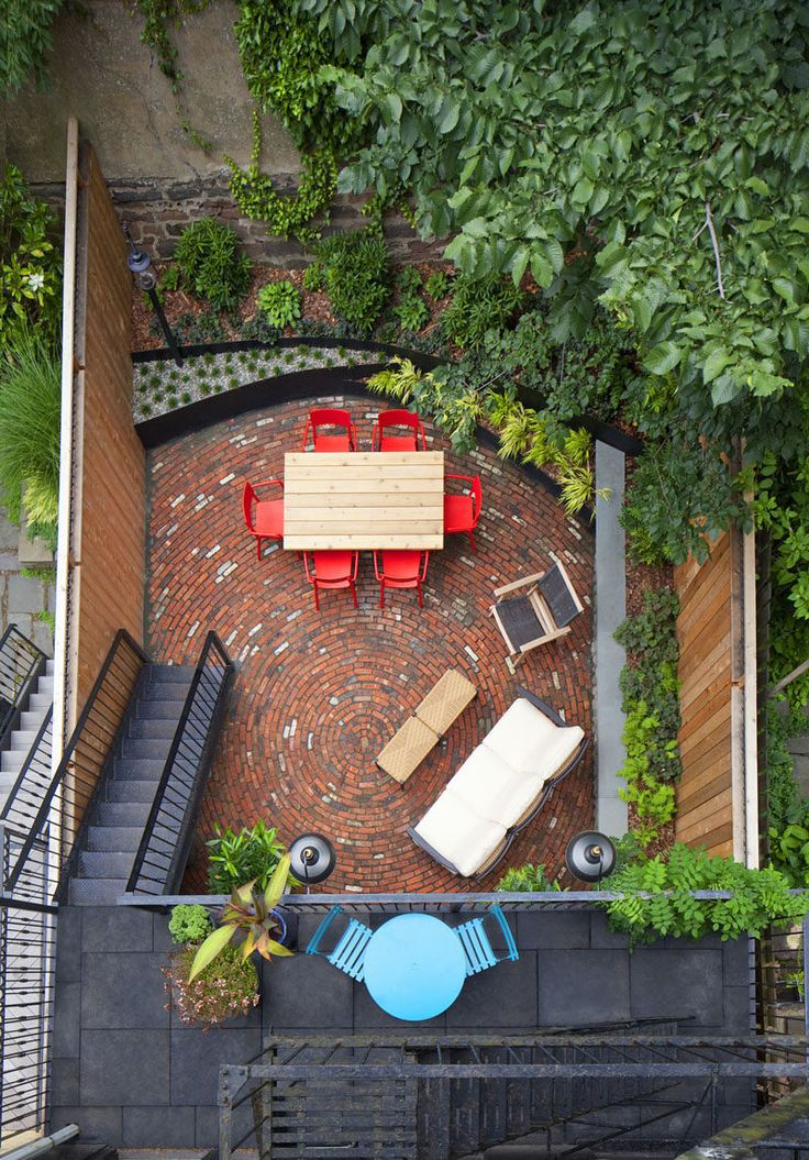 The bright colors of the furniture and the circular brick pattern on this back patio in New York, mix with the surrounding greenery and make for a fun space.