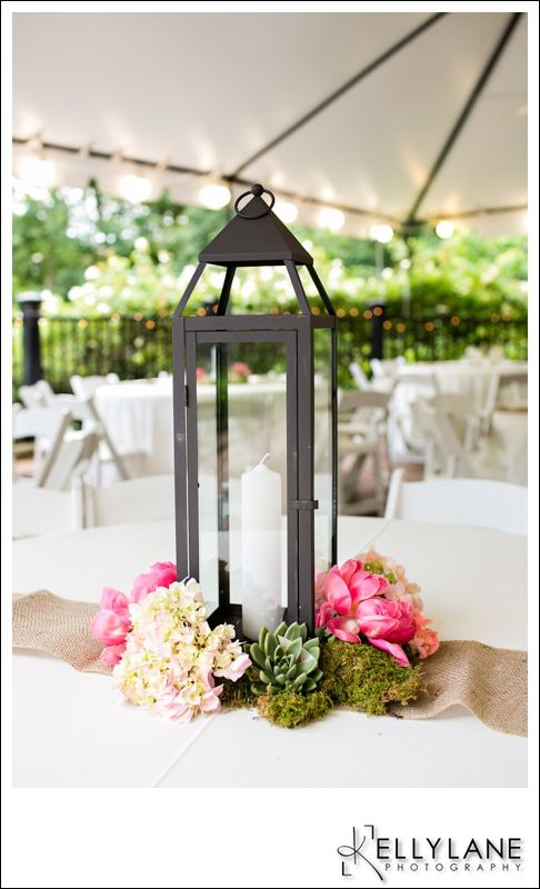 Lantern centerpieces adorned with flowers.