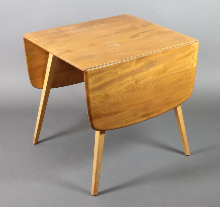 """Lot 982, An Ercol light elm drop flap dining table, raised on 4 square outswept supports 28""""h x 24 1/2""""l when closed x 54""""l when extended x 29""""w, sold for £100"""