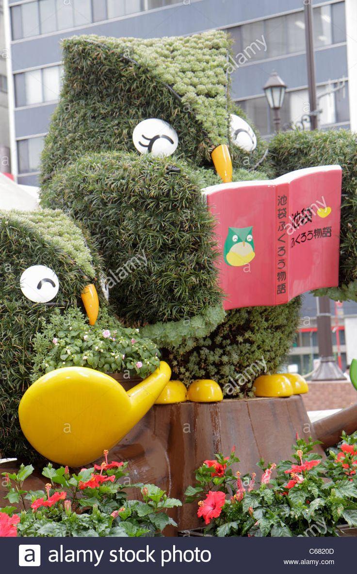 Tokyo Japan Ikebukuro kanji hiragana katakana characters symbols topiary plants shaped like owl owls character reading book city Stock Photo