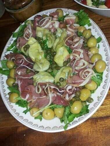 Ensalada de rúcula, jamón crudo, corazón de alcauciles, aceitunas verdes y alcaparras