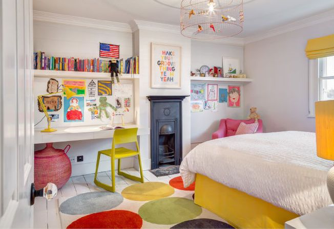 This lovely, bright, and colorful bedroom has a narrow original fireplace that's no longer in use, but kept for architectural detail. The central light is made to look like a bird cage, with colorful birds inside.