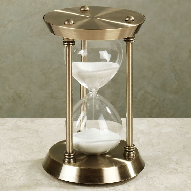 "Watch every half hour pass as sand flows through the Moment in Time Hourglass, and be sure to make every minute count. A unique blend of the traditional and modern, this sand hourglass makes the perfect decorative accent for an office, a desk, or a shelf. Tabletop hourglass measures 6""dia.x9""H. • Stunning metal hourglass has an antique brass finish • Transitional tabletop accent blends with many decor styles"