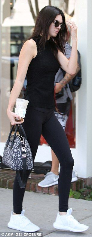 Designer details; She paired the workout pants with a plain black top, Yeezy trainers and a graphic-printed tote