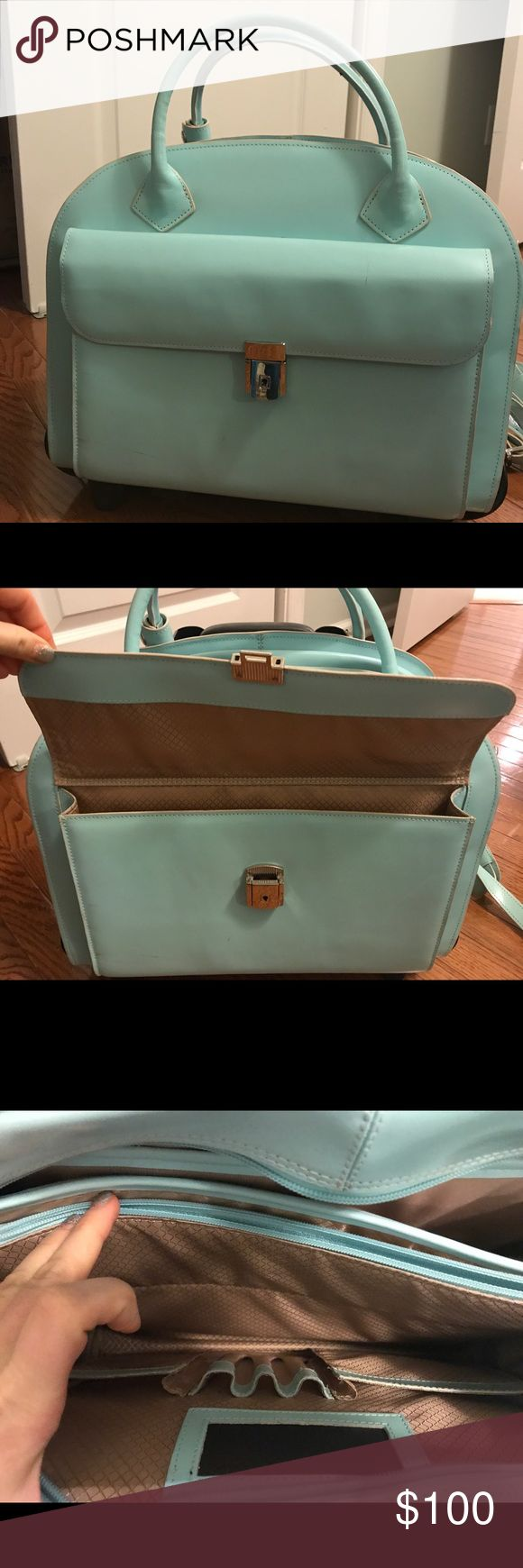 Traveling briefcase/computer bag Aqua. A great briefcase on wheels. Has a ton of storage and padded section for lap top. It includes straps and can also be removed from wheels. Has a waterproof protective covering. Bags Laptop Bags