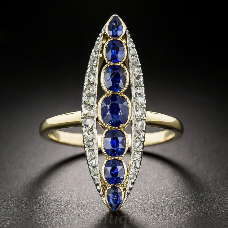 Long Antique Sapphire and Diamond Dinner Ring. This extra-long (just shy of 1 1/4 inch) and extra-lovely Victorian treasure is designed around a radiant row of seven gorgeous royal blue sapphires totaling 2.00 carats. The splendid gemstones are bezel-set and bordered on each side with glistening rose-cut diamonds in an elegantly elongated navette shape dinner ring hand fabricated in platinum over 18K yellow gold