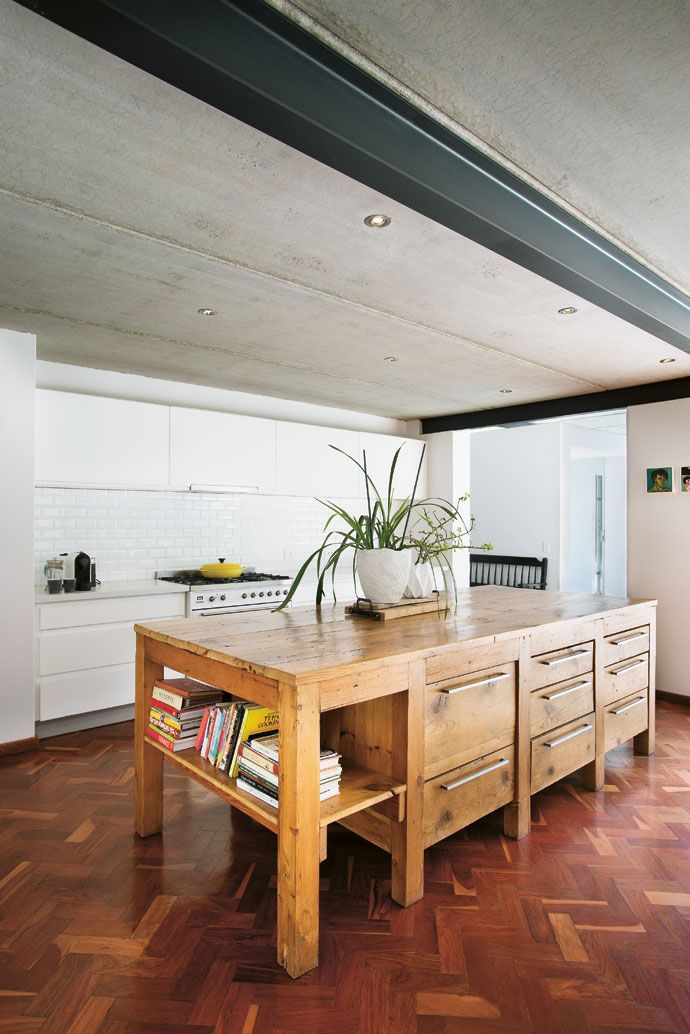 A recycled butcher's table is used as a kitchen island, creating a contrast with the crisp white cupboards.