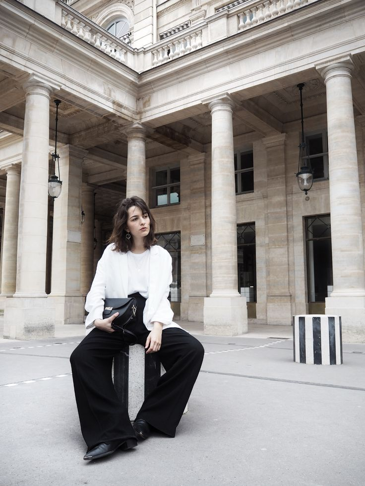 Paris Streetstyle at Palais Royal by Anaïs Eleni wearing Acne Studios Jensen Boots, black wide pants, white Mango blazer and Camelia Roma Celine lookalike bag.