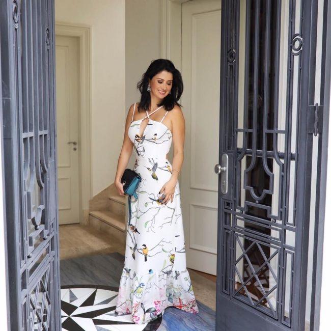 Look de Constanza Fernandez: vestido longo estampado de fundo branco da Maracujá! Nos pés, uma flatform prateada da Paula Torres.