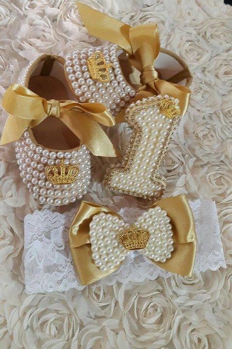 Sapato na cor dourada, com laço de cetim e coroa.  Tamanhos: 17, 18.  Contem 3 peças, sapatinho + faixa de cabelo + enfeite de bolo( não é vela).  Cores: dourado, preto, branco, vermelho, rosa.    Fazemos qualquer outro tamanho por encomenda.