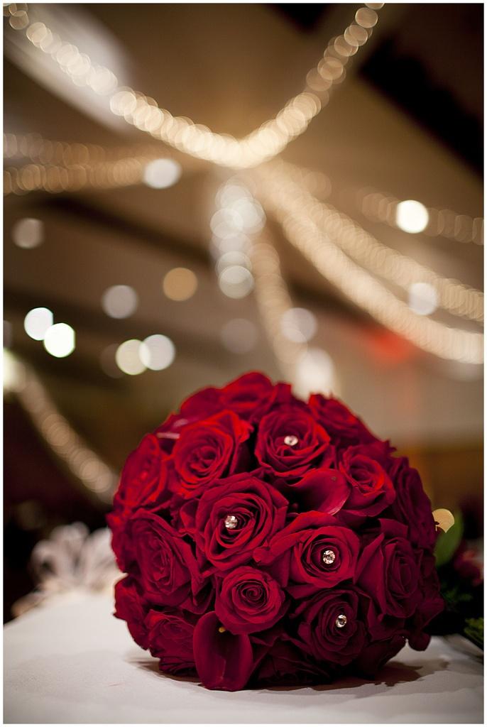 Klassinen punainen ruusukimppu kallalla ja strasseilla höystettynä.